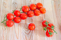 Group of red cherry tomatoes, bunch, vine,  close up, wood backg Stock Image
