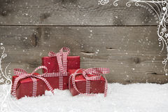 Group of red Christmas presents, with snow on grey