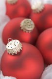Group of red christmas tree decorations. Wrapped in tissue paper Royalty Free Stock Images