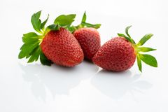 Group of red strawberries with green leaves on white background stock photo
