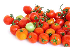 Group of red tomatoes with one green on white background Stock Photo