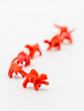 A group of red toy dianosaurs isolated on white royalty free stock photos
