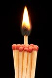 Group of red wooden matches with burning match. In the centre, isolated on black background Royalty Free Stock Images
