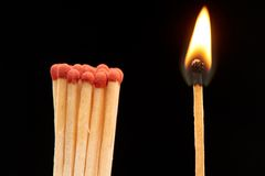 Group of red wooden matches standing with burning match. Isolated on black background Stock Photos