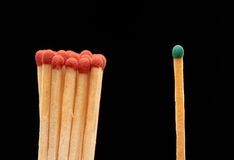 Group of red wooden matches standing with green match. Isolated on black background Royalty Free Stock Photos