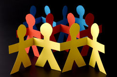A group of red yellow and blue paper men Stock Photo