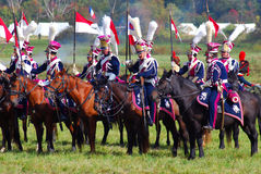 A group of reenactors dressed as Napoleonic war soldiers ride horses Royalty Free Stock Images