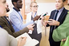 Group of Reporters Taking Interview. International group of journalists asking questions  to mature businessman at press conference taking interview Royalty Free Stock Photos