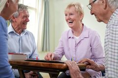 Group Of Retired Friends Playing Board Game At Social Club stock image