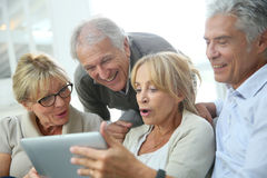 Group of retired people having fun using tablet. Group of retired people sitting in sofa and using tablet Stock Photo
