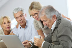 Group of retired people at home using laptop Stock Photos