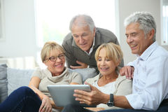 Group of retired people sitting in sofa with tablet Stock Photography