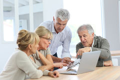 Group of retired people using electronical devices. Group of retired senior people using laptop and tablet Stock Photos
