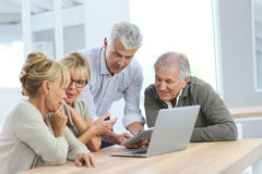 Group of retired people using laptop at home Stock Photography