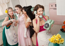 Group Of Retro Housewives. Woman on phone while friends give young woman cigarette and alcohol in a retro styled kitchen scene Stock Image