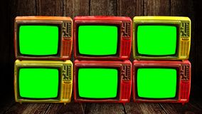 Group of retro television with green screen at wooden floor and wall royalty free stock images