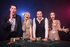 Group of a stylish rich friends are playing poker at casino. Group of a rich friends are playing poker at casino. Youth are making bets waiting for a big win royalty free stock photo