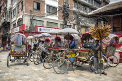 Group of rickshaws by the street at Asan Tole Market which is busy with workers, local and tourists, Kathmandu, Nepal Royalty Free Stock Image