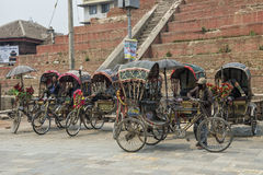 Group of rickshaws by the street at Asan Tole Market which is busy with workers, local and tourists, Kathmandu, Nepal Stock Photos