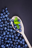 A group of ripe, juicy, organic blueberries with mint in a wooden spoon on a purple background. Raw summer diet. A fantastic composition of fresh, ripe and Stock Photography