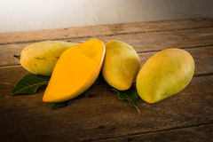 Group of ripe mangoes. On wooden table. vintage tone Stock Image