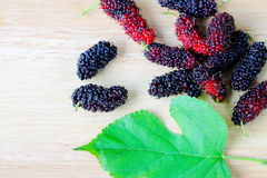Group of ripe mulberry with leaf  on the wooden backgro Stock Photo
