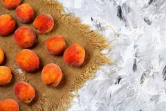 A group of ripe peaches on the old fabric. light background. Fresh peach concept. Flat lay. Copy text royalty free stock photo
