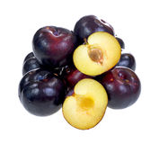 Group of ripe plums with one cut in half Royalty Free Stock Photography