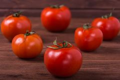 Red ripe tomatoes. The group of ripe tomatoes on wooden background Stock Photos