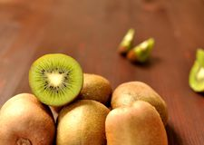 Group of ripe whole kiwi fruit and half kiwi fruit on brown wooden background royalty free stock images