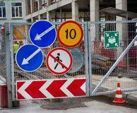 Group of road traffic signs on the metal gate of the construction site stock photo