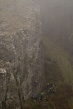 Group of rock climbers in fog at Cheddar Gorge. Team of climbers ascend cliff in Somerset, UK, in one of Britain`s most impressive areas of natural beauty royalty free stock image