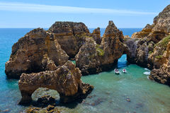 Group of rock formations (Portugal). Group of rock formations along coastline of Lagos town, Ponta da Piedade, Algarve, Portugal. All people in motorboats are Royalty Free Stock Image