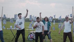 A group of rock musicians explodes simultaneously several firecrackers on the background of their instruments in the field in the. Evening. Cheerful company stock video footage