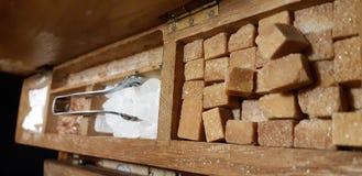 A group of rock sugar. Brown sugar cubes in wooden box . Various tea and various kind of sugar on wooden table. Rock candy sugar in wooden box. Brown sugar cubes stock photo