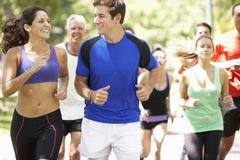 Group Of Runners Jogging Through Park Stock Image