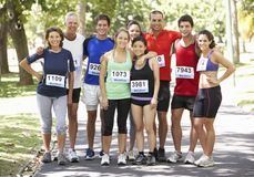 Group Of Runners Jogging Through Park Stock Photo