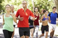 Group Of Runners Jogging Through Park Stock Photography