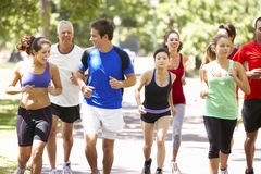 Group Of Runners Jogging Through Park Stock Photos