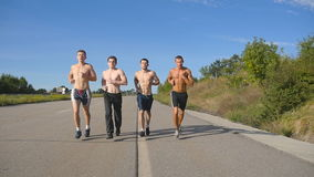 Group of runners men jogging at highway. Male sport athletes training outdoor at summer. Young strong muscular guys stock footage