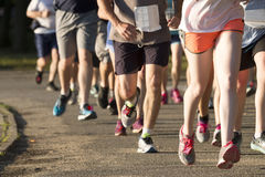 Group of runners racing a 5K on a dirt path royalty free stock photos