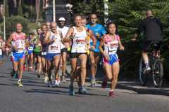 Group of runners on the road (Hunger Run 2014, FAO/WFP). A group of runners on the road when cornering. Sunny and warm day. Historic Centre of Rome, Italy. The Royalty Free Stock Photos