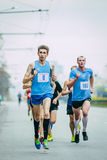 Group of runners running down a city street Royalty Free Stock Photography