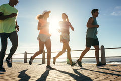 Group of runners running on road by the seaside. On a sunny day. Healthy young people training together outdoors royalty free stock photo