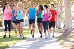 Group Of Runners On Suburban Street. Running Towards Camera stock images