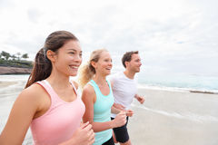 Group running on beach jogging. Exercising runners and friends training outdoors living healthy active lifestyle. Multiracial fitness runner people working out Royalty Free Stock Photos
