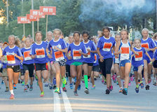 Group of running girls in blue dresses Stock Photo
