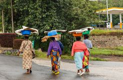 Group of Rwandan women in colorful traditionals clothes wearing washbowls on their heads, Kigali, Rwanda. Adult africa african basin black chores colored royalty free stock photo