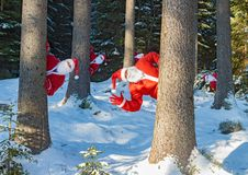 Group of Santa Claus greets behind snowy trees. stock photo