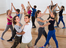 Group of satisfied teenagers dancing tango in dance studio stock photo